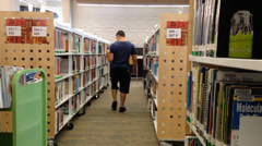 Librarian putting books back to shelf inside library. Stock Footage