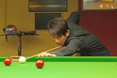 Young man concentrating while aiming at pool ball while playing billiards. Stock Photos