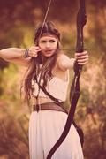 Woodland hunter woman with bow and arrow Stock Photos