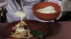 Cook flavoring dessert pancakes with cream and fruit jelly - stock footage