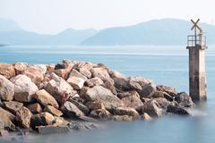 Lighthouse on a Rocky Breakwall: A small lighthouse warns of a rough shoreline. Stock Photos