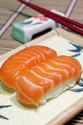Yummy salmon. A close-up of chopsticks and a square plate with two pieces of sal Stock Photos