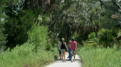 Young couples walk sandy foot path Stock Footage