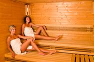 Stock Photo of Sauna two women relaxing sitting wrapped towel