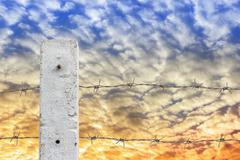 rusty barbed wire fence with cloud and sky. - stock photo