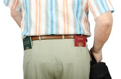 tourist holding tonga and russian passports in rear pockets - stock photo