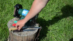 Knife sharpening with special grinder tool on outdoor log grass Stock Footage
