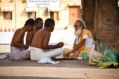 hindu brahmin with religious attributes providing ceremony and blessing pilgrim - stock photo