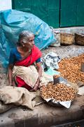 indian women selling peanuts at street market place  - stock photo
