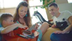 young, attractive family playing guitar and singing songs - stock footage