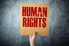 Man holding cardboard paper with HUMAN RIGHTS title Stock Photos
