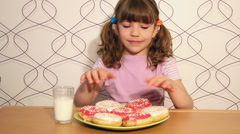 Hungry little girl eating donuts Stock Footage