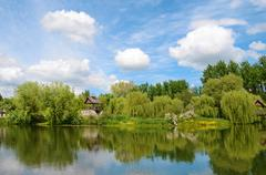 Fairytale landscape with pond and beautiful clouds on a sunny day Stock Photos