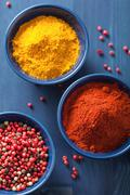 Stock Photo of spices in bowls: curry pink and black pepper paprika powder
