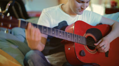 Young, attractive man sitting playing guitar Stock Footage
