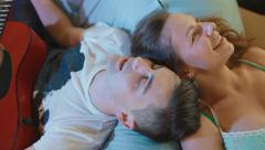 Romantic, attractive couple musicians supine each other head compose a new song Stock Footage
