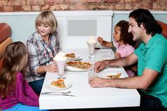 Cheerful family of four enjoying breakfast - stock photo