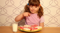Little girl eating donuts Stock Footage