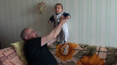 Grandpa puts small baby on legs Stock Footage