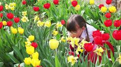 Little girl playing in the tulips Stock Footage