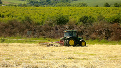 SBig green tractor with hay maker working on the meadow in farmland. Haymaking Stock Footage