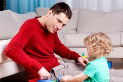 Smiling father playing with his son Stock Photos