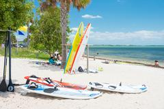 surfboards and people enjoying the beach in miami - stock photo