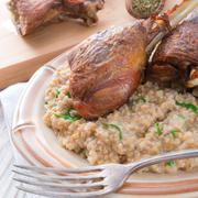 roasted goose thighs with grits - stock photo