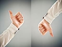 Businessman showing thumb up and thumb down symbol Stock Photos