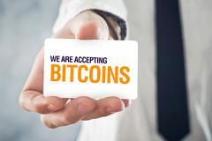 Businessman holding card with title WE ARE ACCEPTING BITCOINS - stock photo
