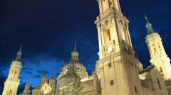 Main towers of Zaragoza Basilica against cloudy dark blue evening sky Stock Footage