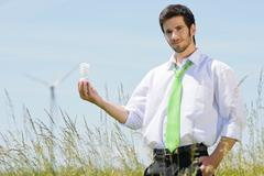 Green energy businessman in field hold bulb - stock photo