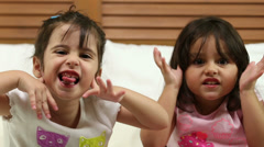 Small girls making a funny face in the bedroom - stock footage