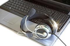 Headphones on notebook surface - stock photo