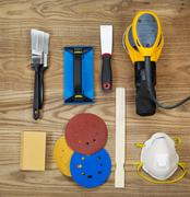 sanding and painting accessories on faded wooden boards - stock photo