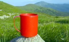Red cup on stone in mountains camp Stock Photos