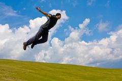 Man jump over meadow - stock photo