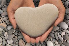 Female hands holding a heart-shaped stone Stock Photos