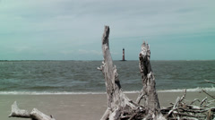 Drift wood and light house in ocean Stock Footage