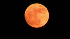 Orange full moon over dark sky Stock Footage