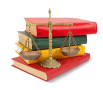 Scales of justice atop legal books over white Stock Photos