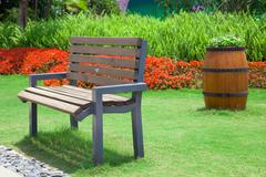 Beautiful summer garden with bench and big decorative wooden flo - stock photo