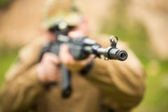 man in camouflage with a shotgun aiming at a target. focus on hole - stock photo