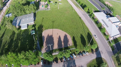 Aerial rural town youth softball game in park HD 032 Stock Footage