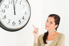 Punctual businesswoman attractive point at clock - stock photo