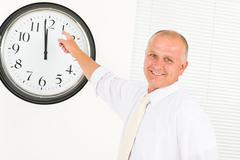 Stock Photo of Punctual businessman mature point at clock