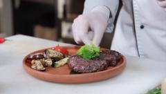 Steak gets taken off barbecue, chef presenting dish on plate, click for HD Stock Footage