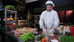 Smiling cook making sushi rolls on a rolling bamboo mat, click for HD Stock Footage