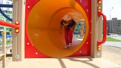 Active little girl playing on a training equipment, running in tunnel Stock Footage