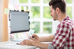 overworked man with stickers on computer - stock photo